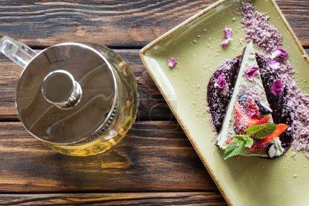 vue de dessus de dessert végétarien arrangé avec baies sur la plaque et la théière sur la surface en bois