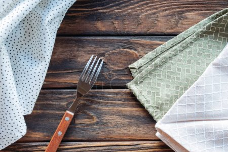 top view of linen and fork on wooden surface