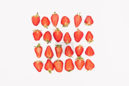 top view of fresh cut strawberries in rows isolated on white background