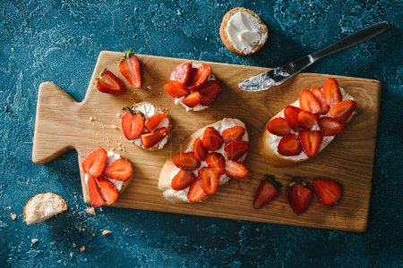 Cooking summer sandwiches with strawberries and soft cheese on wooden board