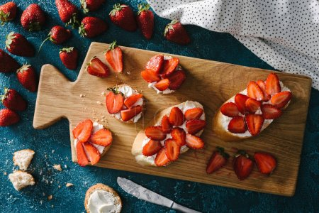 top view of fresh strawberries by wooden board with summer sandwiches