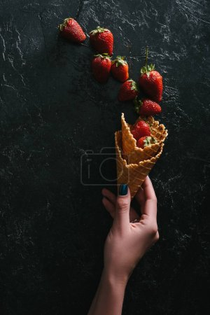 Woman holding waffle cones with raw strawberries on dark background