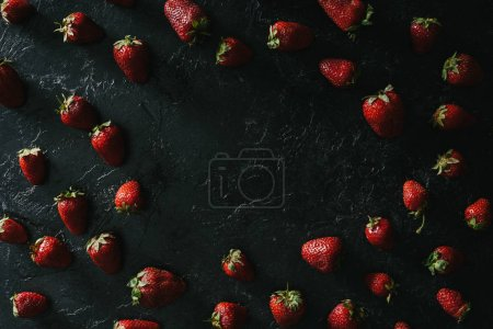 Frame of raw juicy strawberries on dark background