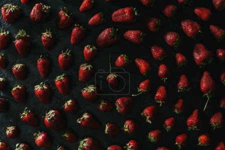 Spiral composition of red strawberries on dark background