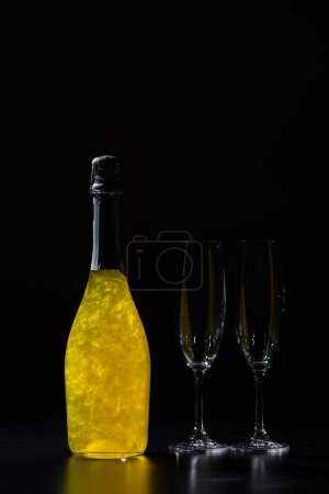 close up view of bottle of champagne and empty glasses on black background