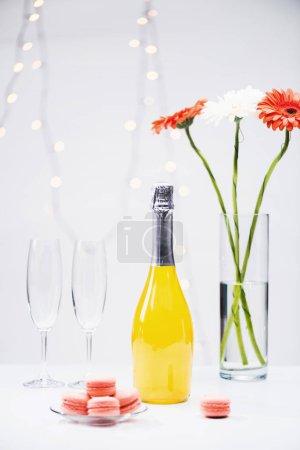 Photo pour Bouchent la vue des macarons, des verres vides, bouteille de champagne et un bouquet de gerbera fleurs sur fond gris - image libre de droit