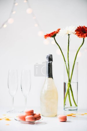 close up view of macarons, empty glasses, bottle of champagne and bouquet of gerbera flowers on grey backdrop