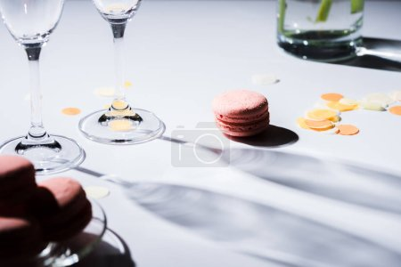 close up view of arranged sweet macarons and empty glasses on tabletop
