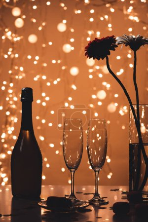 close up view of bottle of champagne, empty glasses and bouquet of flowers on tabletop