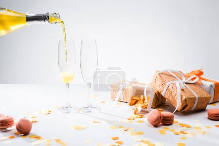 close up view of pouring yellow champagne into glasses process, macarons and arranged gifts on grey backdrop