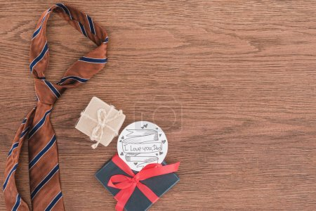 top view of tie with gifts and Happy fathers day greeting on wooden surface