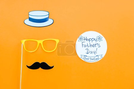 top view of gentleman face with Happy fathers day greeting card on yellow surface