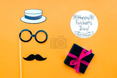 top view of gentleman face with Happy fathers day greeting card and gift on yellow surface