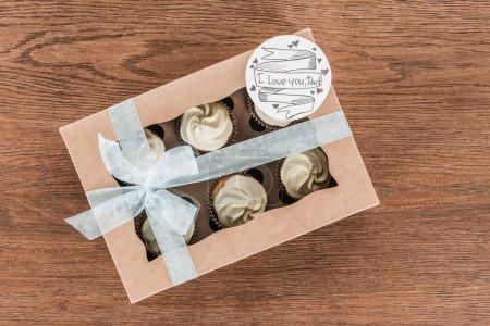 Photo pour Vue du haut de la boîte avec de savoureux cupcakes dans la boîte avec je t'aime papa carte de vœux, concept de fête des pères heureux - image libre de droit