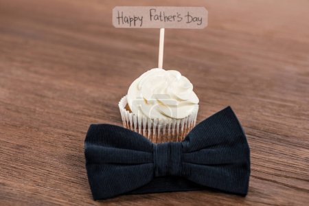 tasty cupcake with bowtie and Happy fathers day inscription on wooden surface