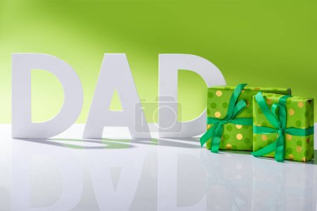 green gift boxes in front of dad inscription made of white letters on green, Happy fathers day concept