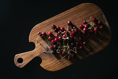 top view of fresh ripe red cherries on wooden cutting board isolated on black