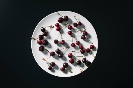 top view of fresh ripe red cherries on round white plate isolated on black