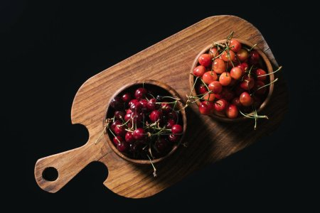 Photo for Top view of sweet ripe red and yellow cherries in bowls on wooden cutting board isolated on black - Royalty Free Image