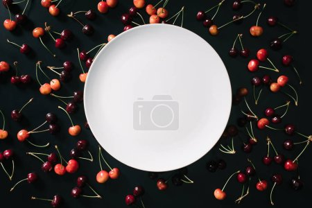 top view of empty round white plate and sweet cherries on black