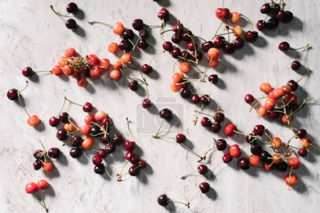 top view of fresh ripe healthy cherries on marble background