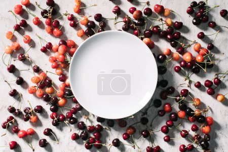 top view of empty round white plate and ripe sweet cherries on white