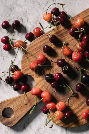 top view of fresh ripe sweet cherries on wooden cutting board on marble surface