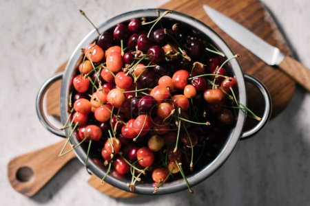 top view of metallic pan with ripe sweet cherries on wooden cutting board with knife