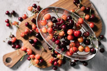 top view of sweet ripe cherries on vintage plate and wooden cutting board on white, selective focus
