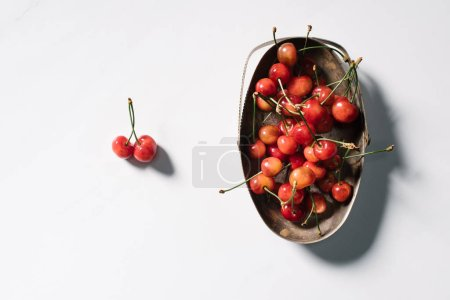 top view of tasty healthy organic cherries in vintage bowl on white