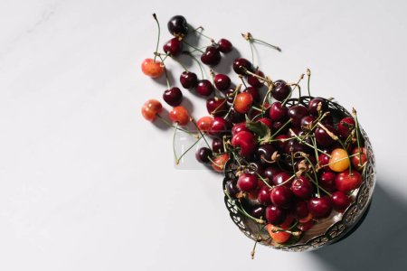 top view of fresh ripe sweet cherries in vintage bowl on white