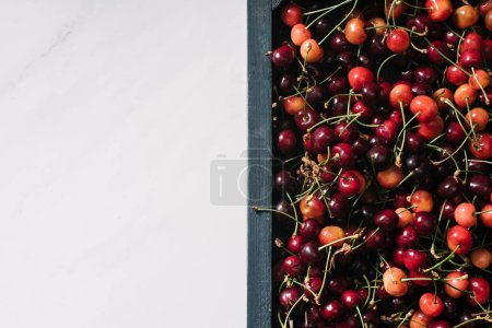 top view of tasty healthy organic cherries in wooden box on white
