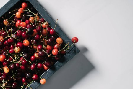 Photo for Top view of fresh ripe sweet cherries in wooden box on white - Royalty Free Image