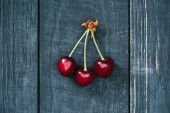 top view of tasty healthy red cherries on rustic wooden surface