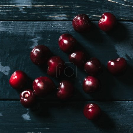 top view of red ripe cherries on wet wooden surface