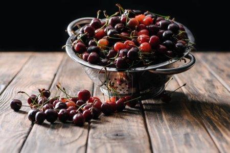 fresh ripe sweet cherries in colander on wooden table