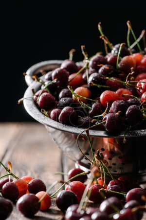 close-up view of fresh ripe wet cherries in colander on wooden table