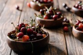 close-up view of fresh ripe sweet cherries in bowls on wooden table
