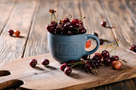 Photo for Close-up view of ripe fresh sweet cherries in blue cup on wooden cutting board on table - Royalty Free Image
