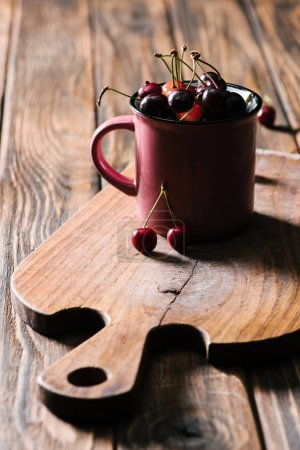 healthy tasty cherries in pink cup on wooden cutting board on table