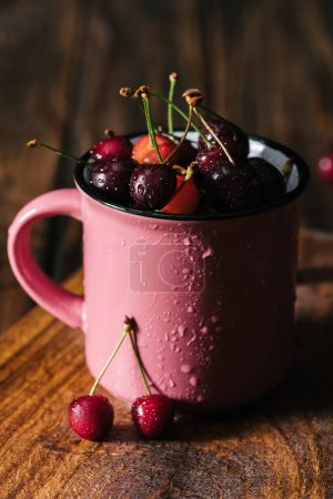 close-up view of fresh ripe cherries in wet pink cup on wooden table