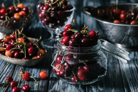 close-up view of fresh ripe cherries in glass jar, colander and utensils on rustic wooden table