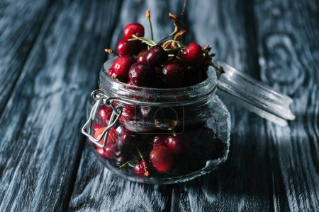 close-up view of ripe sweet healthy cherries in glass jar on wooden table