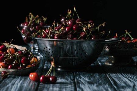 ripe sweet healthy cherries in colander on wooden table