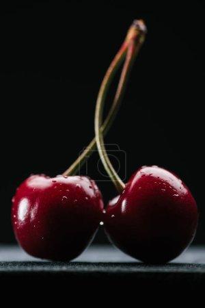 close-up view of fresh wet sweet cherries on black