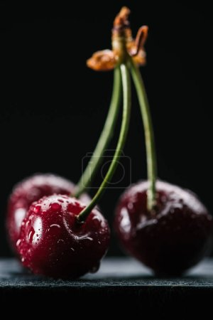 close-up view of fresh sweet healthy cherries with water drops on black