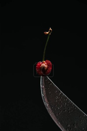 close-up view of half of ripe sweet cherry on knife isolated on black