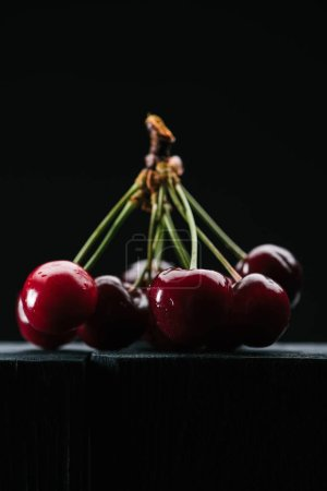 close-up view of ripe sweet cherries on wooden tabletop on black