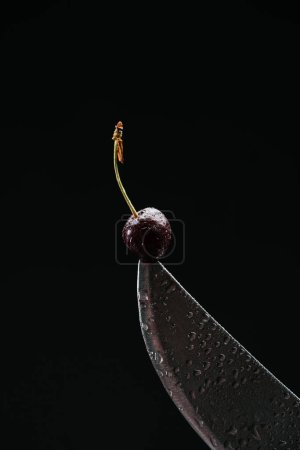 close-up view of single ripe sweet cherry on knife isolated on black