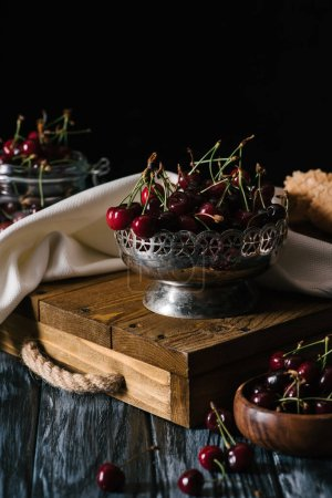 close-up view of sweet organic cherries in vintage bowl on wooden table